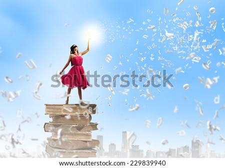 Young woman in blindfold standing on pile of books - stock photo