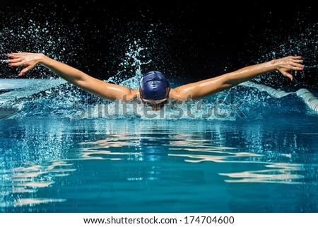 Young woman in blue cap and swimming suit in pool - stock photo