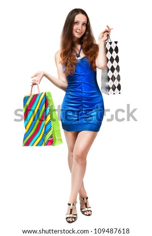 Young woman in blue dress with colorful shopping bags on a white background