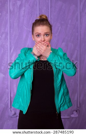 Young woman in blue jacket close the mouth with her hands on a purple background - stock photo