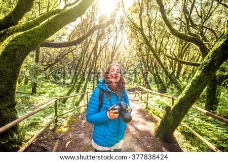 Young woman in blue jacket traveling with backpack, photographing with photo camera beautiful evergreen forest in Garajonay park on La Gomera island on Canary island, in Spain - stock photo