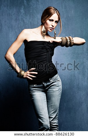 young woman in blue jeans and oriental jewelry studio shot - stock photo