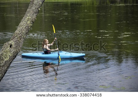 Young woman in blue kayak, paddling right from behind a tree trunk on Mud Pond in Sunapee, New Hampshire, on a sunny day, horizontal image. - stock photo