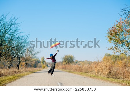 Young woman in blue retro hat, with colorful umbrella jumping high on empty autumn road copy space background - stock photo
