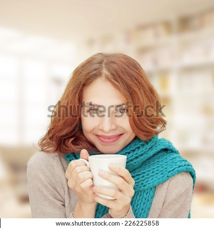 young woman in blue scarf with white mug, indoor - stock photo