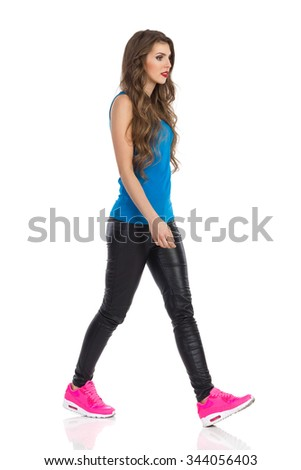 Young woman in blue shirt, black leather trousers and pink sneakers walking and looking away. Full length studio shot isolated on white.
