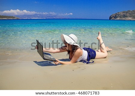 young woman in blue skirt using laptop on wet sand at beach