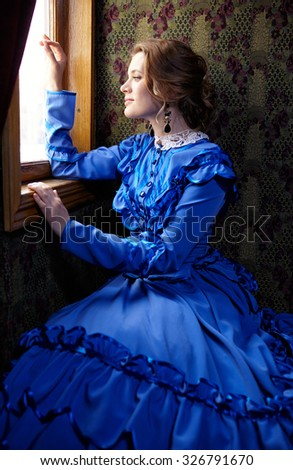 Young woman in blue vintage dress late 19th century looking out the window in coupe of retro railway train