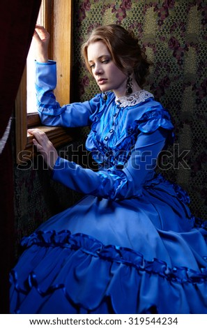Young woman in blue vintage dress late 19th century sitting in coupe near the window of retro railway vehicle