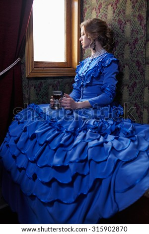 Young woman in blue vintage dress late 19th century sitting in coupe of retro railway train, looking out the window and drinking tea - stock photo