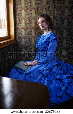 Young woman in blue vintage dress late 19th century sitting with book in coupe of retro railway vehicle