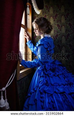 Young woman in blue vintage dress late 19th century standing near window in coupe of retro railway train