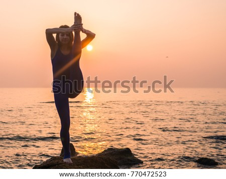 Young Woman in Bodysuit Practicing Yoga on the Beach at Amazing Sunrise.