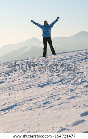 Young woman in bright clothes is standing on a hillside covered with snow and  up her hands.  The range of Carpathian Mountains (Europe) is in the background.