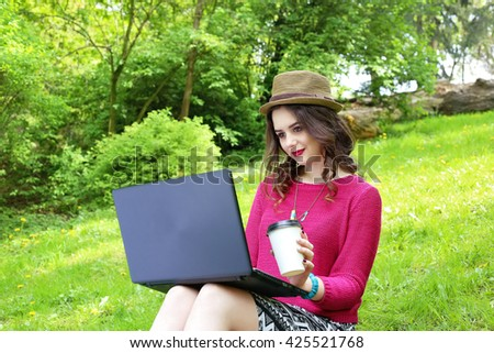 Young woman in bright pink knitted sweater and hat sitting on the lawn and working on her notebook. Woman with coffee paper cup using laptop and typing. Freelancer concept