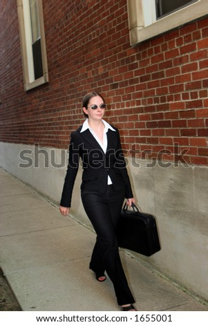 Young woman in business attire, carrying briefcase and walking up sidewalk by a brick building.