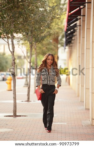 Young woman in business attire walking down the street