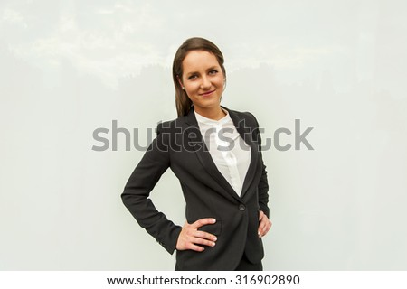 Young woman in business outfit over the glass wall in the city smiling at camera. - stock photo