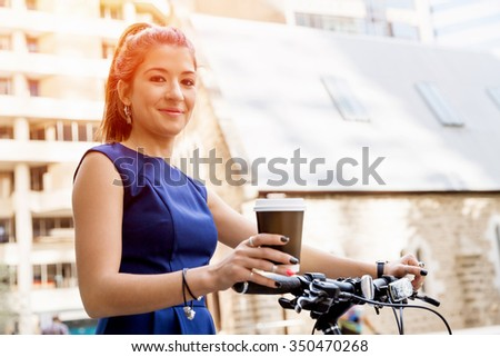 Young woman in business wear on bicycle with a cup of coffee - stock photo