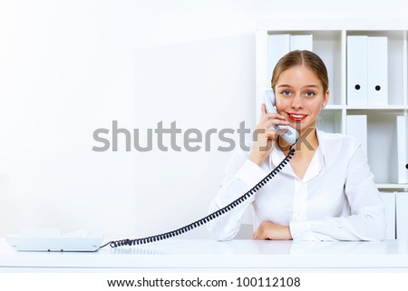 Young woman in business wear sitting with a phone in office - stock photo