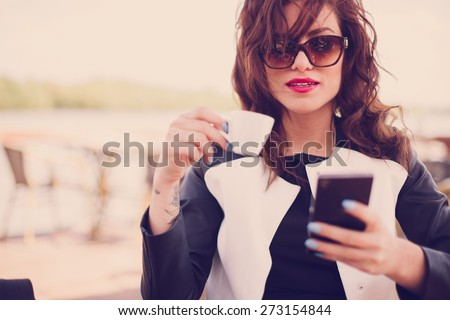 Young woman in cafe, drinking coffee and using her mobile phone - stock photo