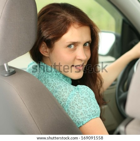 young woman in car - indoor keeps wheel turning around looking at passengers sitting side idea of taxi driver talking to policeman companion companion who asks for directions right drive Documents - stock photo