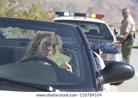 Young woman in car reading ticket with traffic cop in the background - stock photo