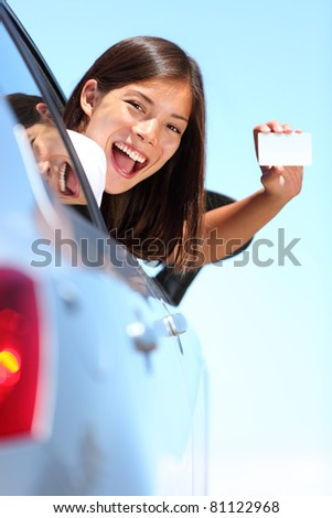 Young woman in car showing blank drivers license or sign out the car window. Happy lovely mixed race Asian Caucasian female model outside.