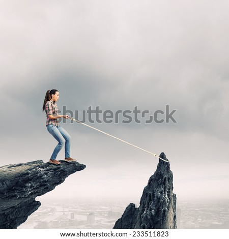 Young woman in casual catching rock with rope