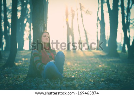 young woman in casual clothes rest by tree in forest retro colors - stock photo