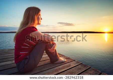 Young woman in casual clothing sitting on wooden bridge and looking on sunset over lake. - stock photo
