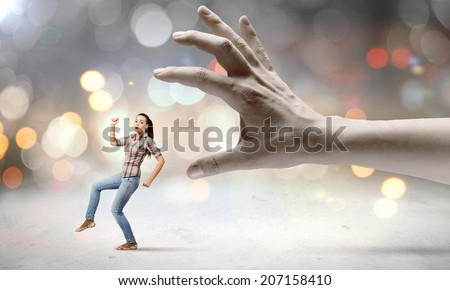 Young woman in casual escaping from big male hand - stock photo