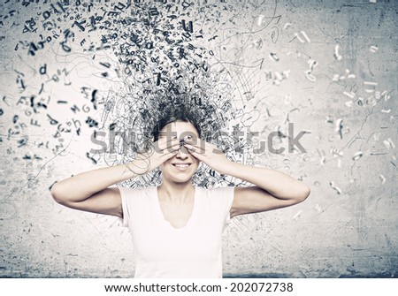 Young woman in casual hiding eyes behind palms - stock photo