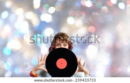 Young woman in casual holding disco plate on bokeh background