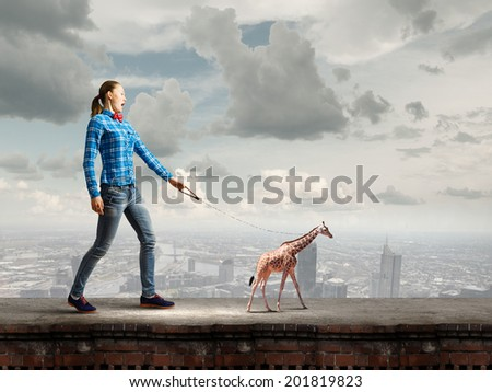 Young woman in casual holding giraffe on lead