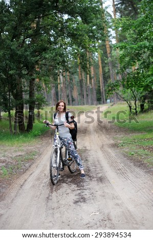 Young woman in casual outfit on bike standing on  forest road and looking to somewhere - stock photo