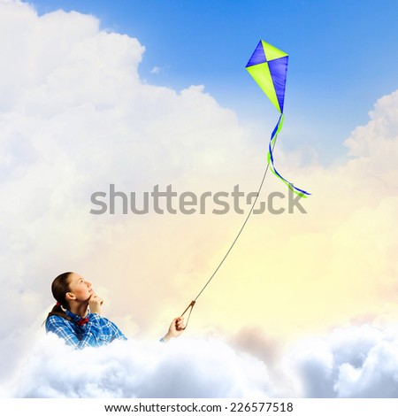 Young woman in casual playing with kite