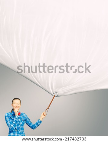 Young woman in casual pulling white blank banner. Place for text