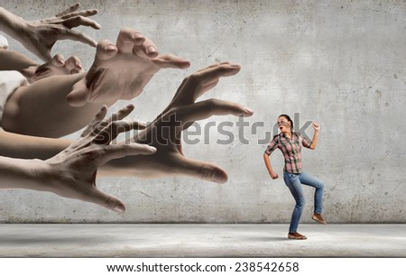 Young woman in casual running away from big hand - stock photo