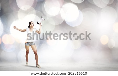 Young woman in casual talking in megaphone