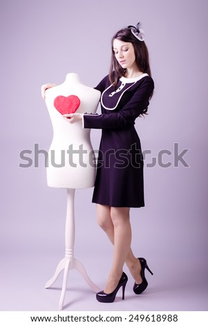 Young woman in classic black dress giving heart to mannequin studio background - stock photo