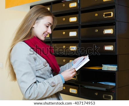 Young woman in coat checking correspondence at lobby