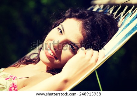 Young woman in cocktail dress relaxing in a hammock on sunny day. - stock photo