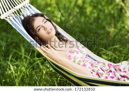 Young woman in cocktail dress relaxing in a hammock over sunny background. - stock photo