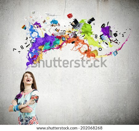 Young woman in colorful dress looking at light bulb - stock photo