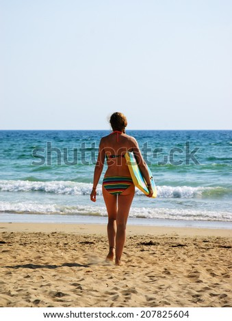 Young woman in colorful striped swimsuit  walking towards a water holding a surf board . Back view. (Brittany, France)  Freedom concept - stock photo