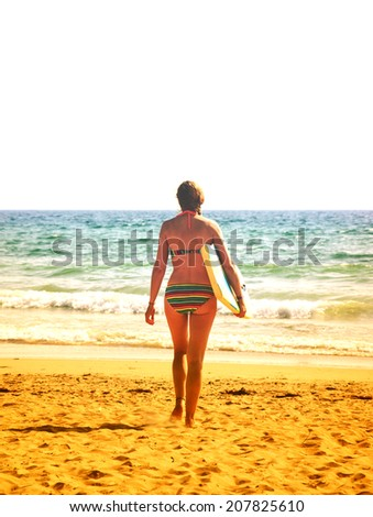 Young woman in colorful striped swimsuit  walking towards a water holding a surf board . Back view. (Brittany, France) Aged photo. Freedom concept. - stock photo