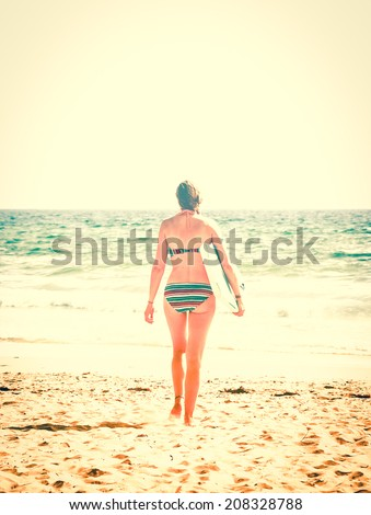 Young woman in colorful striped swimsuit  walking towards a water holding a surf board . Back view. (Brittany, France) Freedom concept. Aged photo. - stock photo