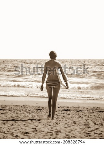 Young woman in colorful striped swimsuit  walking towards a water holding a surf board . Back view. (Brittany, France) Freedom concept. Aged photo. Sepia. - stock photo