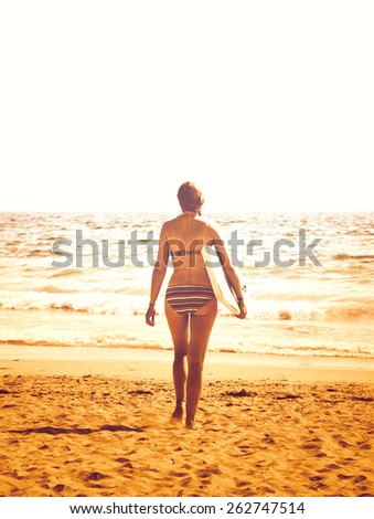 Young woman in colorful striped swimsuit  walking towards a water holding a surf board. Back view. (Brittany, France) Toned vintage photo. - stock photo